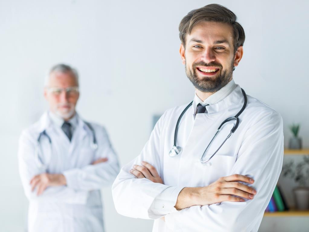 """Ein junger Arzt steht vor einem alten Arzt. Dabei ist der Fokus auf den jungen Arzt gesetzt. Es symbolisiert eine Praxisübernahme. Bei einer Praxisübernahme macht unser Angebot """"komplette mediale Praxisausstattung"""" sehr viel Sinn."""